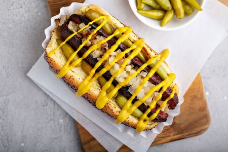 Hot dog on a poppy seed bun, topped with onions, mustard and hot peppers