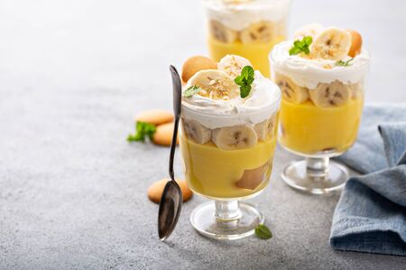 Banana pudding layered dessert with vanilla wafers in small glasses