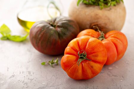 Ripe and fresh heirloom tomatoes with olive oil and herbs