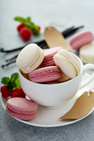 Vanilla and raspberry french macarons in a teacup Stock Photo