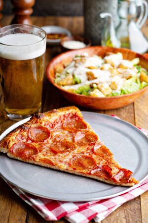 Pepperoni pizza slice with a side salad and a glass of beer