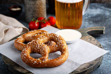 Salty pretzels with cheese sauce and beer