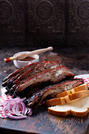 Barbeque smoked beef brisket with BBQ sauce on dark background