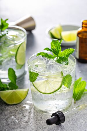 Refreshing summer mojito cocktail with aromatic bitters in a dropper