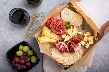 Cheese and meat assortment in a to go box Imagens
