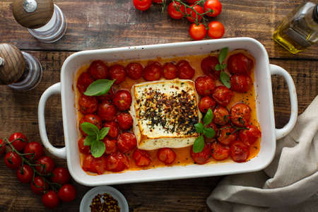 Baked feta cheese with cherry tomatoes in a pan Standard-Bild
