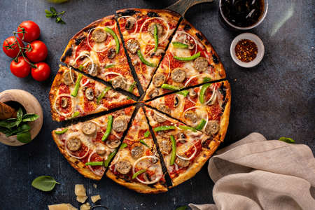 Sausage and vegetable pizza on dark background