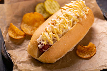 Hot dog with sauerkraut and mustard on parchment Standard-Bild