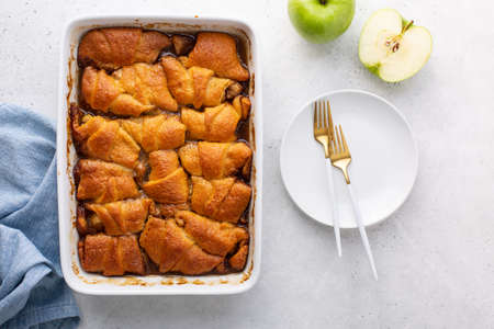 Apple dumplings baked in white dish, overhead shot