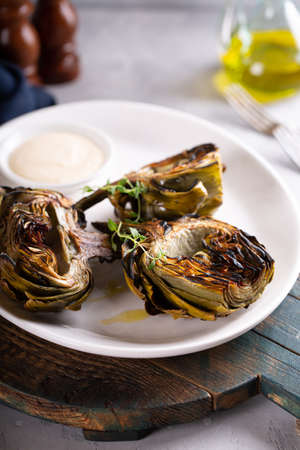 Grilled artichokes with a dipping sauce on a plate Standard-Bild