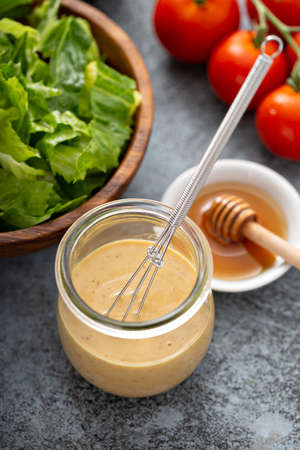 Homemade honey mustard dressing in a glass jar