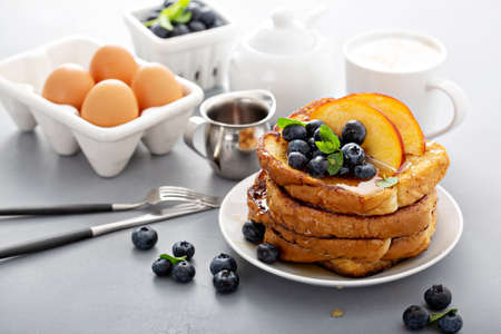 Stack of french toast with fresh peaches and blueberry Standard-Bild
