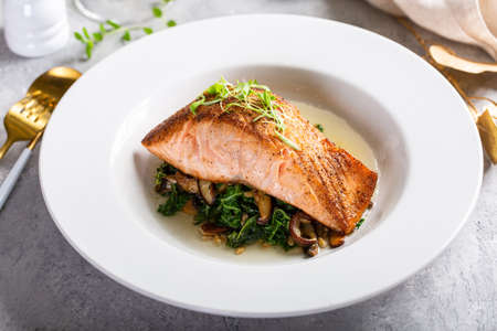 Salmon fillet served with sauteed greens and mushrooms