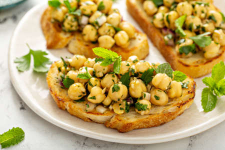 Healthy bruschetta with chickpea salad and herbs