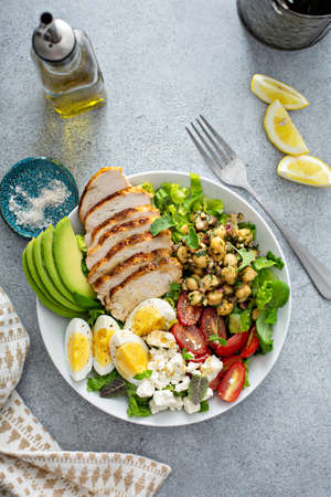 Healthy salad lunch bowl with chicken, avocado and chickpeas