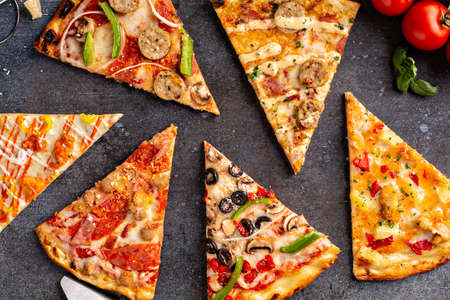 Variety of pizza slices top view on dark background