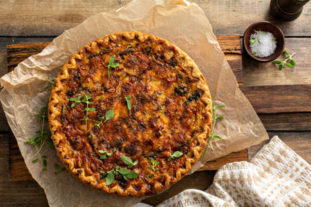 Bacon, mushroom and spinach quiche with cheese and herbs