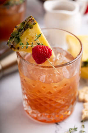 Raspberry pineapple refreshing cocktail with thyme sprig