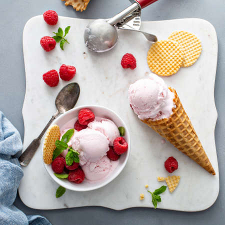 Raspberry ice cream in a bowl and conw with fresh berries