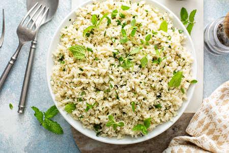 Cauliflower rice with herbs and lemon juice in a white bowl 版權商用圖片