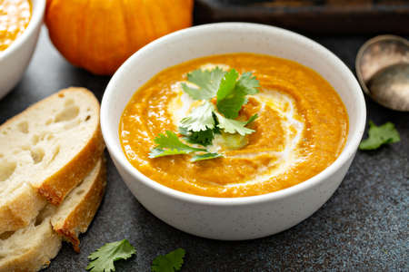 Pumpkin soup served with cream and cilantro