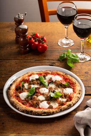 Pizza Napolitana or Naples style with mozzarella, basil and sausage
