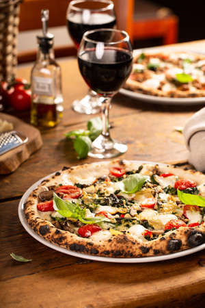 Pizza Napolitana or Naples style with mozzarella, mushrooms and spinach