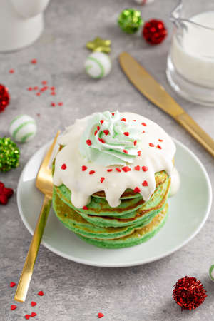 Green pancakes served with white glaze and whipped cream