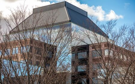 View of the top of a modern business corporate building  and bare trees against the blue sky in Quincy, Massachusetts 版權商用圖片