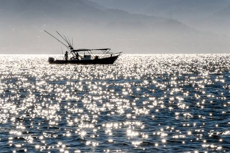 Distant silhouette of a fishing boat amid sparkles in the sea, Puerto Vallarta, Jalisco, Mexico, early morning 版權商用圖片 - 140585834