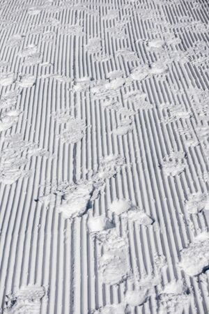 Vertical abstract background with human footprints in the snow