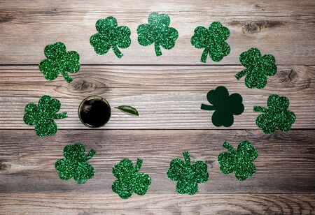Flat lay composition with clover leaves and glasses of beer on wooden background. Saint Patrick's day