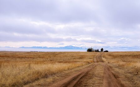 Beautiful Colorado landscape with a meadow, road, farm house, and famous Pikes Peak in the distance 版權商用圖片