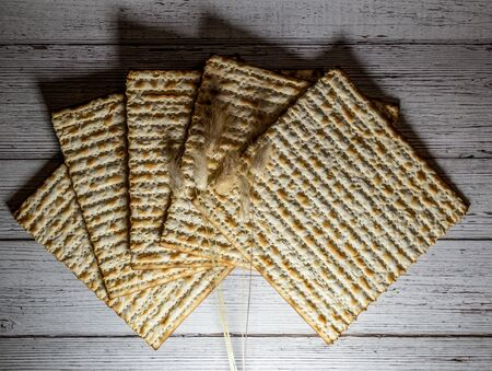 Passover matzos and dried flowers on wooden background