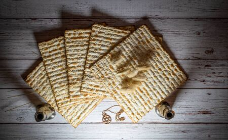 Passover matzos, two candlesticks, dried flowers, and star of David necklace on wooden background