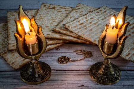 Passover matzos, two candlesticks with burning candles, and star of David necklace on wooden background 版權商用圖片