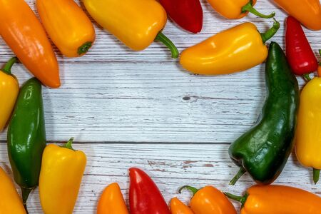 Group of whole fresh pepper flatlay on a wooden background