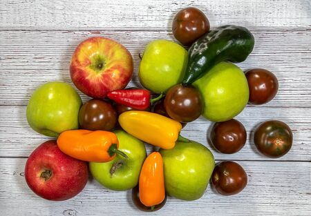 Group of  fresh apples, tomatoes, and pepper flat lay on a wooden background