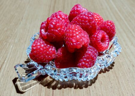 Fresh raspberries in a crystal plate on a wooden background