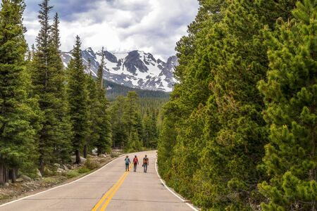 Unrecognizable tourists walking on the road to Brainard Lake and Indian Peaks near Nederland, Colorado, on a spring day 版權商用圖片