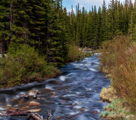 South Saint Vrain Creek flowing into the Brainard lake near Nederland, Colorado, on a spring day
