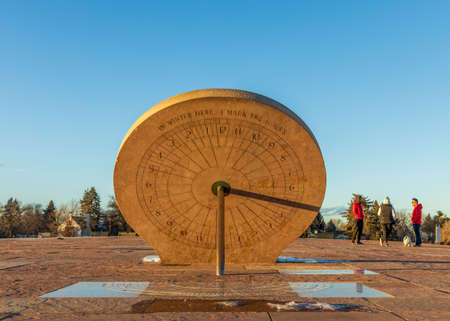 Denver, Colorado - February, 19. 2021: Beautiful sundial in the Cranmer Park, Denver, Colorado, with people, trees, and Denver cityscape on background 新聞圖片