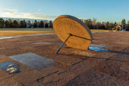 Beautiful sundial in the Cranmer Park, Denver, Colorado, with people, trees, and Denver cityscape on background