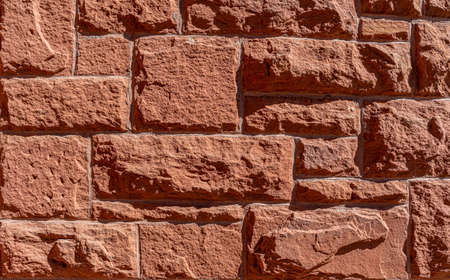 Red hand-made brick wall background. Abstract pattern with inequalities. Close up view to red brick texture. 版權商用圖片