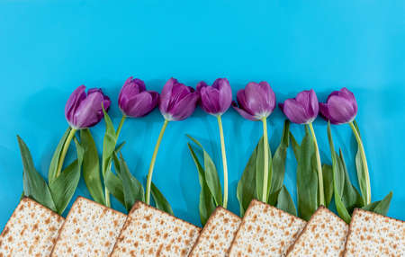 Matzos and flowers on the blue background. Passover (Pesach) Seder