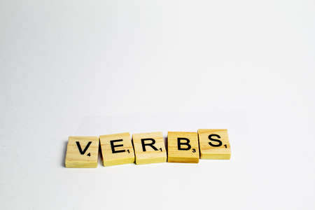 english letters: Scrabble tiles with word verbs written in a white background