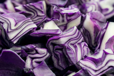 A portion of a red cabbage disposed on a white background