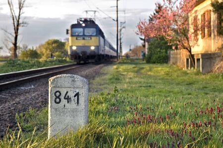 milestone: Milestone with old house and train
