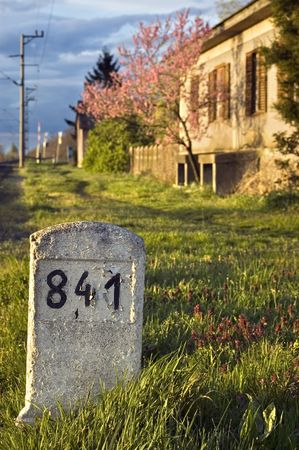 Milestone with old house photo
