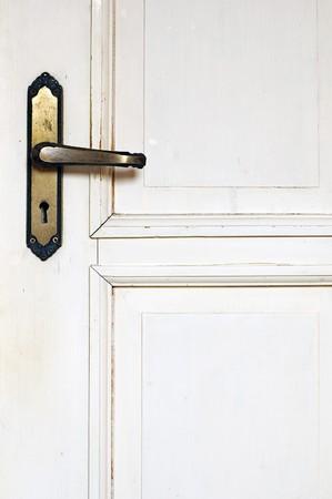 Old rustic wooden white door detail with door handle photo